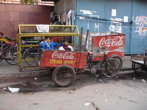 Coca Cola ad on the side of bicycle rickshaw.